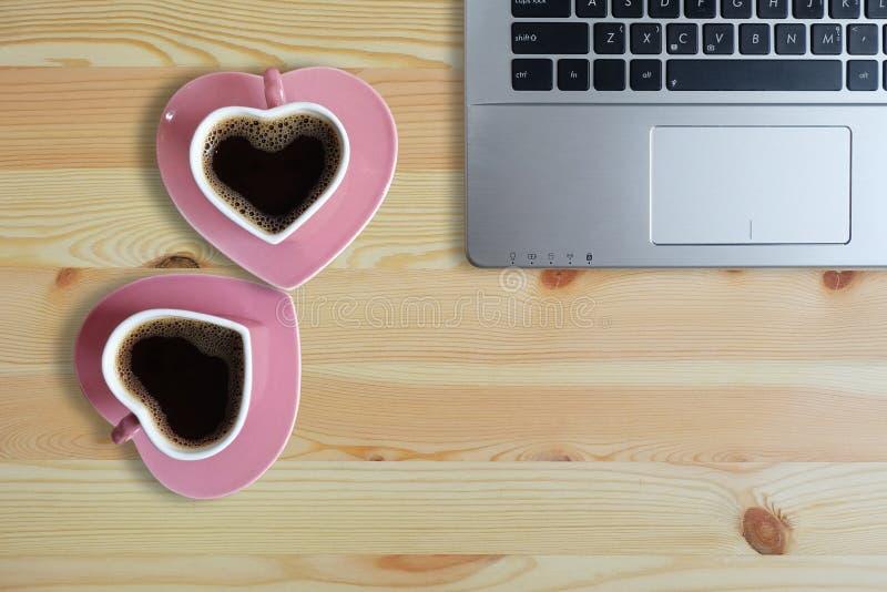 在两个桃红色杯子心形和手提电脑的无奶咖啡在木地板、拷贝空间或者空的空间上文本的 库存照片