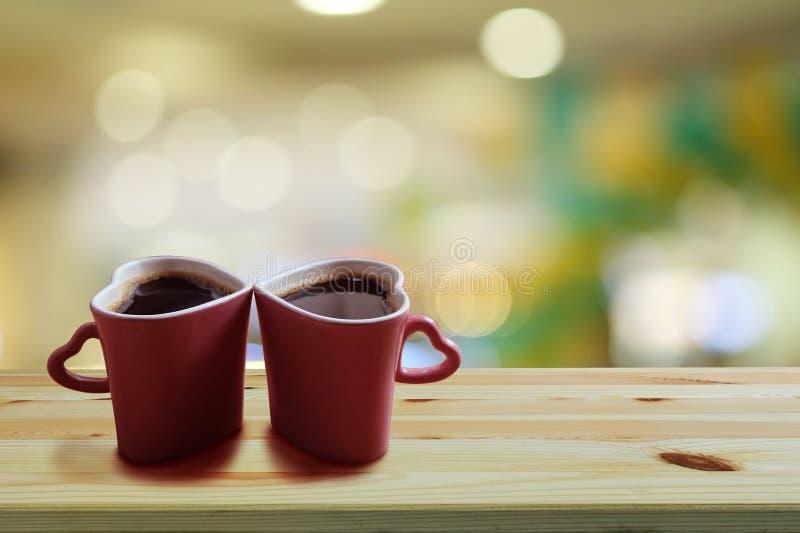 在两个桃红色杯子心形在木地板和五颜六色的bokeh背景上,拷贝空间或者空的空间的无奶咖啡文本的 免版税库存照片