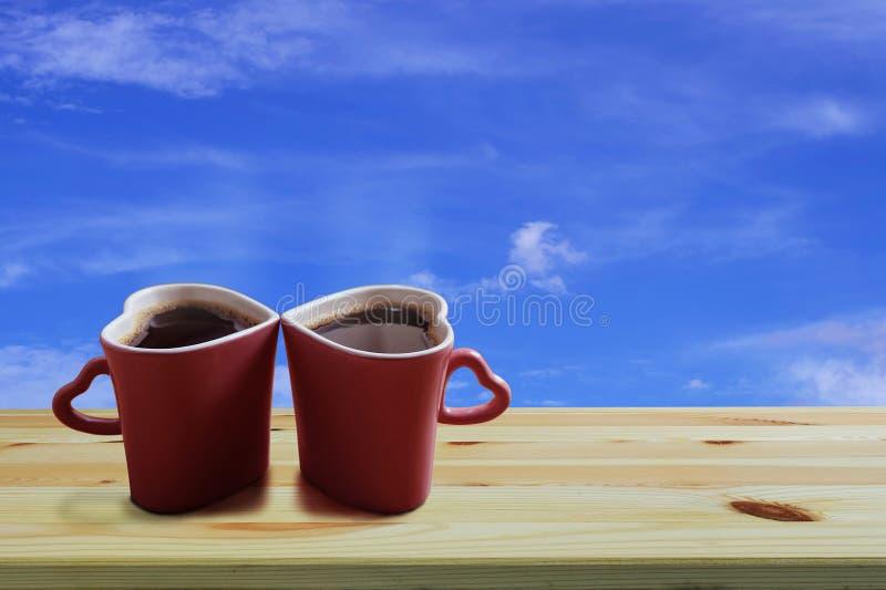 在两个桃红色杯子心形在木地板和天空蔚蓝背景上,拷贝空间或者空的空间的无奶咖啡文本的 图库摄影