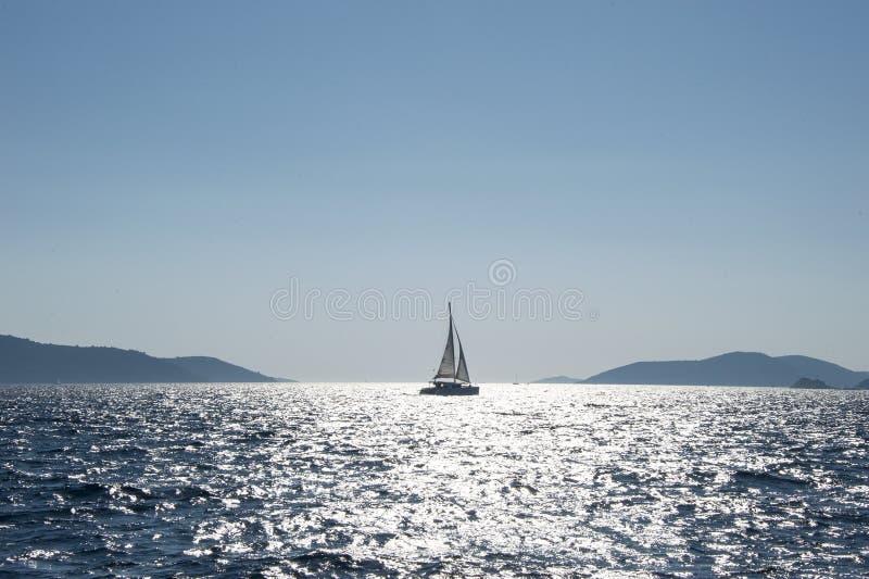 在两个海岛之间的风船在克罗地亚 免版税库存照片