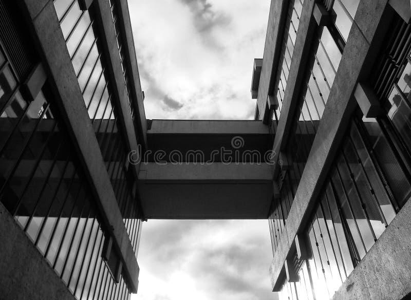 在两个现代混凝土建筑之间的一座桥梁 免版税库存照片