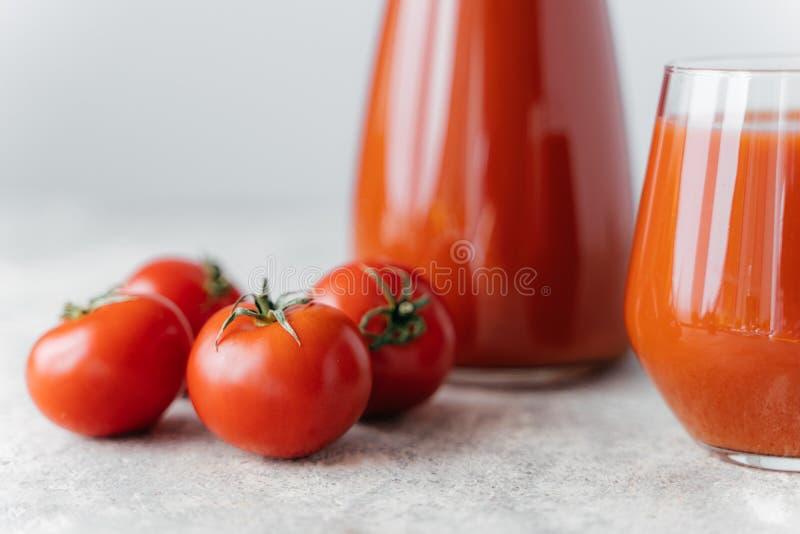 在两个玻璃杯子和小成熟红色蕃茄的西红柿汁在白色背景 包含维生素的新鲜的饮料 r 库存照片