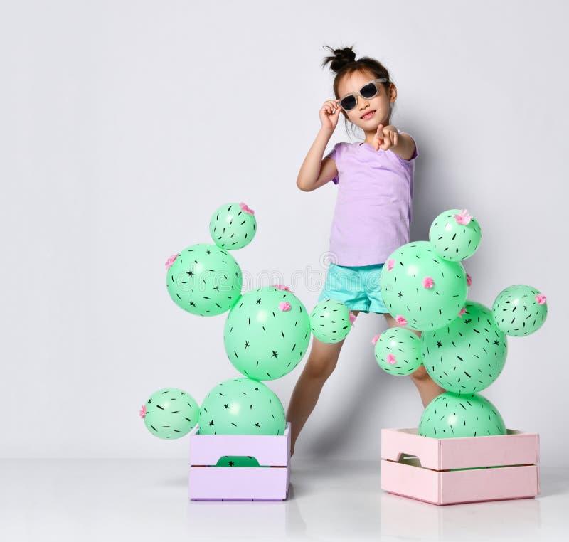 在两个花箱子的凉快的亚洲女孩孩子太阳镜立场有有桃红色花的仙人掌气球的和指向她的fingeat我们 免版税库存图片