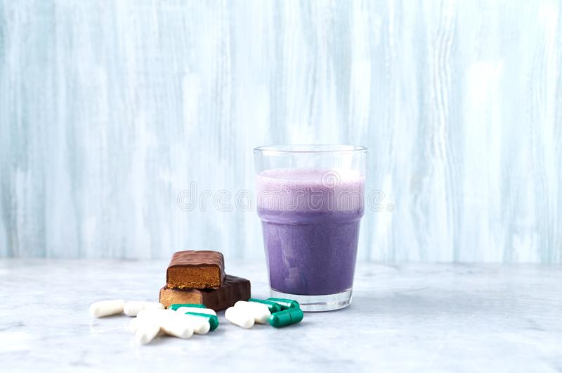 在两个蛋白质震动片断、玻璃用牛奶和蓝莓,L肉毒碱和Beta胺基代丙酸胶囊的蛋白质酒吧在背景中 免版税库存图片