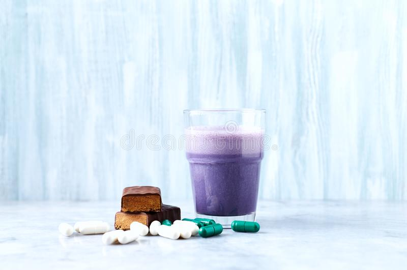 在两个蛋白质震动片断、玻璃用牛奶和蓝莓,L肉毒碱和Beta胺基代丙酸胶囊的蛋白质酒吧在背景中 库存照片