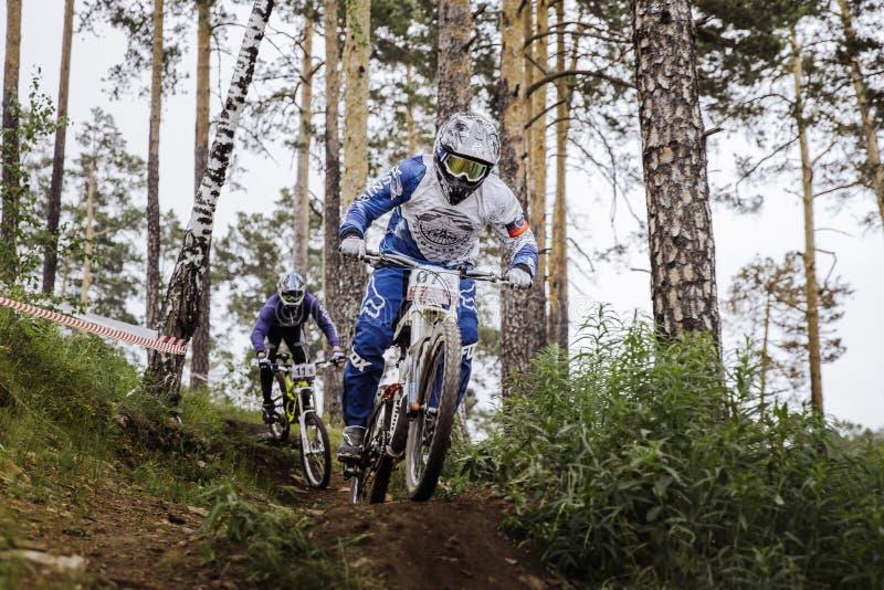 在两个运动员山骑自行车的人之间的竞争轨道的 免版税库存照片