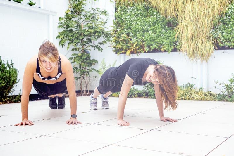在两名正面妇女大阳台的户外锻炼  库存照片