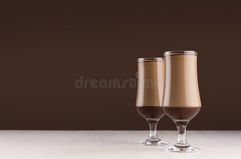 在两块典雅的玻璃的乳脂状的咖啡鸡尾酒用在白色桌和黑褐色墙壁上的巧克力 库存照片