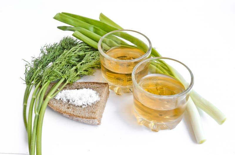 在两块透明玻璃、大葱、莳萝、黑麦面包和粗盐-静物画的胡椒伏特加酒 库存照片