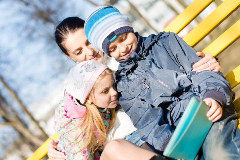 在两孩子漂亮的孩子、儿子和女儿的特写镜头有他们的母亲的获得乐趣使用片剂个人计算机计算机在公园 免版税库存图片