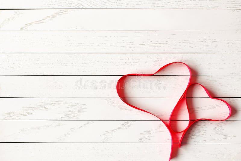 在两心脏形状的红色缎带在木背景的 库存图片