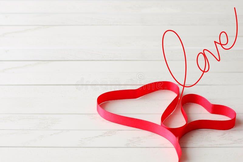 在两心脏形状的红色缎带在木背景的 免版税库存图片