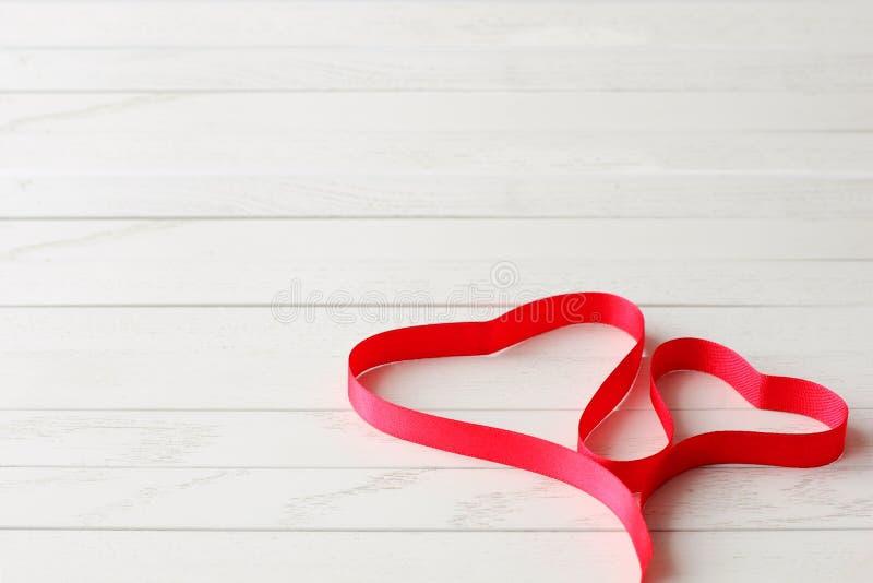 在两心脏形状的红色缎带在木背景的 免版税库存照片
