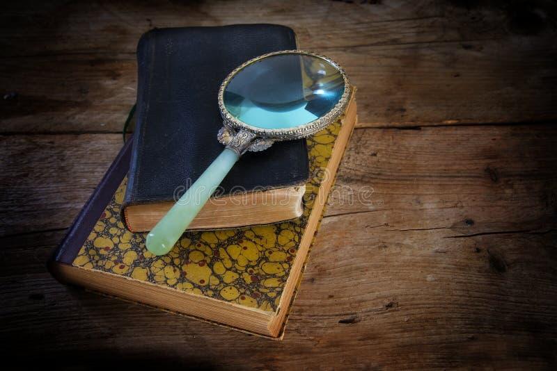 在两本古色古香的书的葡萄酒放大镜, scienc的标志 免版税库存图片