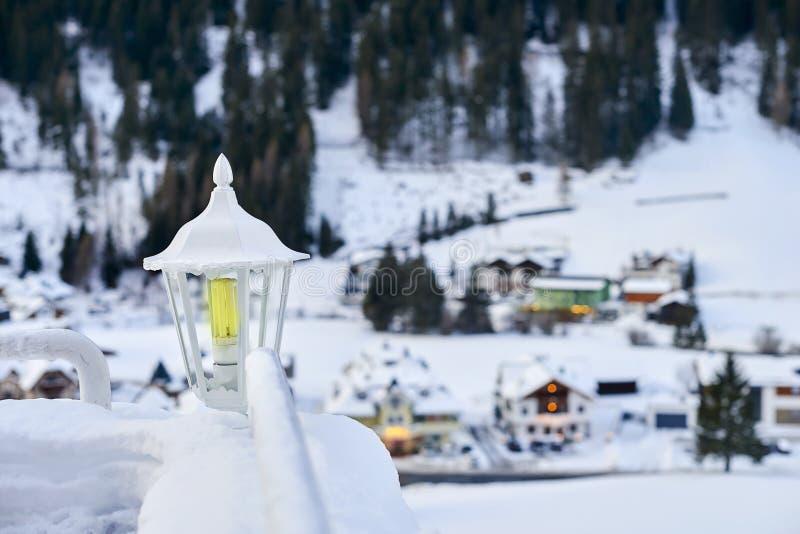 在两栏杆之间的积雪的灯笼与蒂罗尔阿尔卑斯在背景的滑雪胜地 免版税库存图片