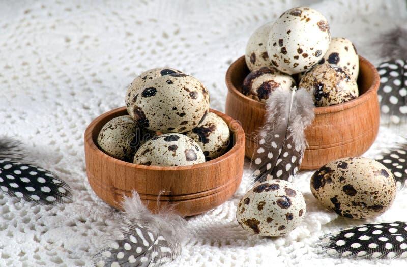 在两根木碗和羽毛的鹌鹑蛋 库存图片