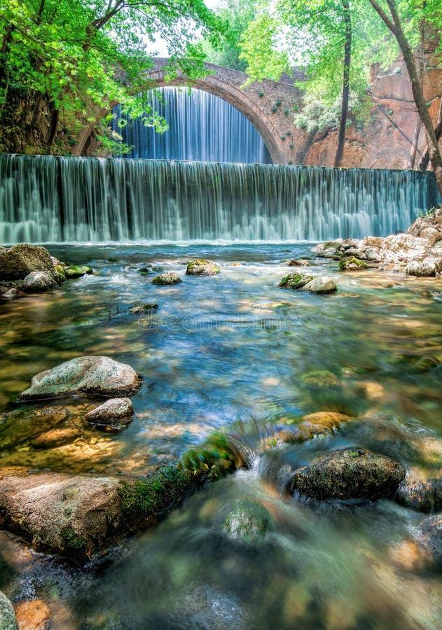 在两瀑布之间的美丽的老石桥梁在Paleokaria特里卡拉希腊 免版税图库摄影