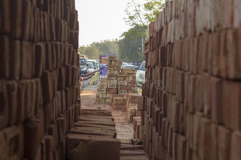 在两被弄脏的砖红色墙壁在街道交通和堆的看法砖之间 免版税库存图片