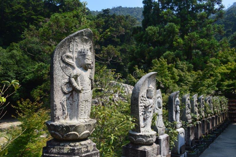 在严岛神社走道的石佛教雕象 库存照片