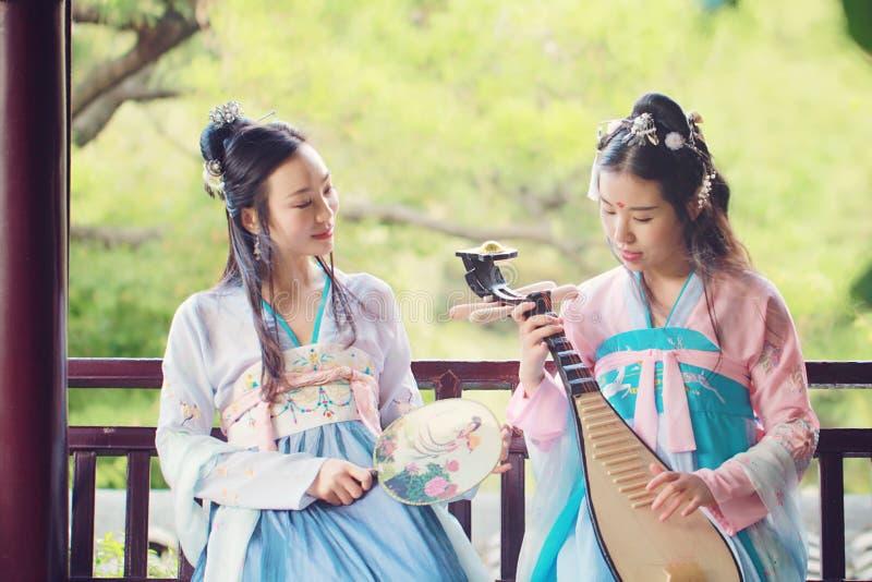 在中国传统古老服装戏剧负子蟾琵琶吉他的接近的女朋友bestie 库存图片