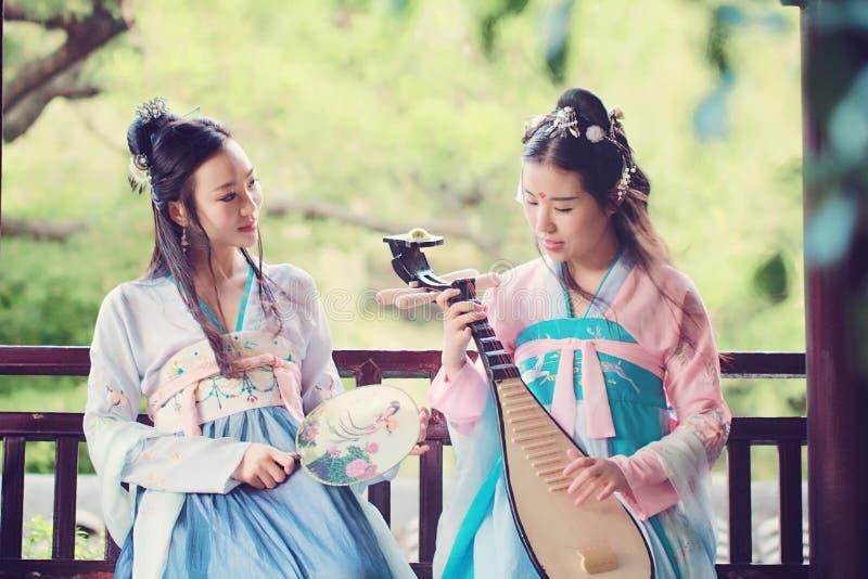 在中国传统古老服装戏剧负子蟾琵琶吉他的接近的女朋友bestie 图库摄影