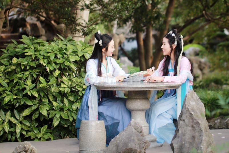 在中国传统古老服装闲谈谈话笑的接近的女朋友bestie 库存图片