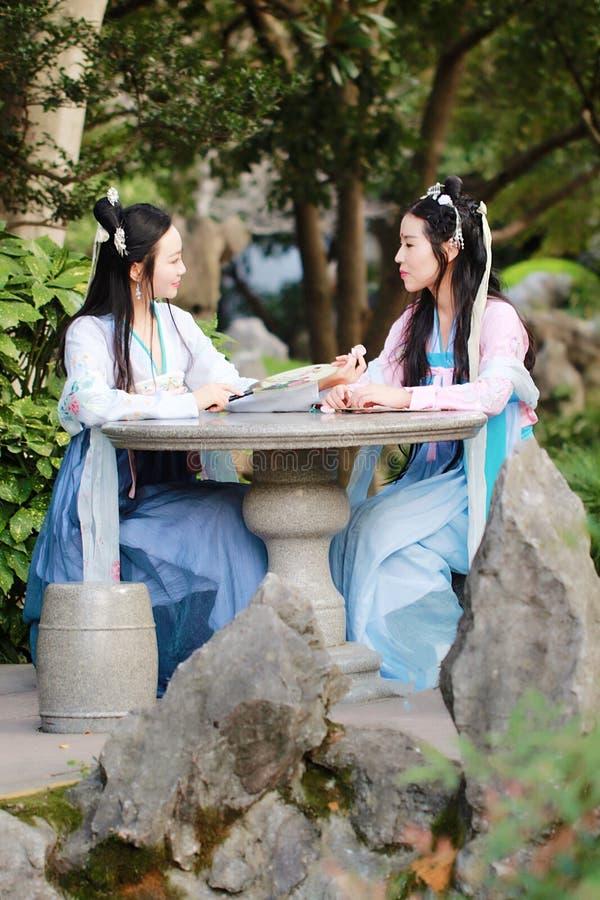 在中国传统古老服装闲谈谈话笑的接近的女朋友bestie 免版税库存照片