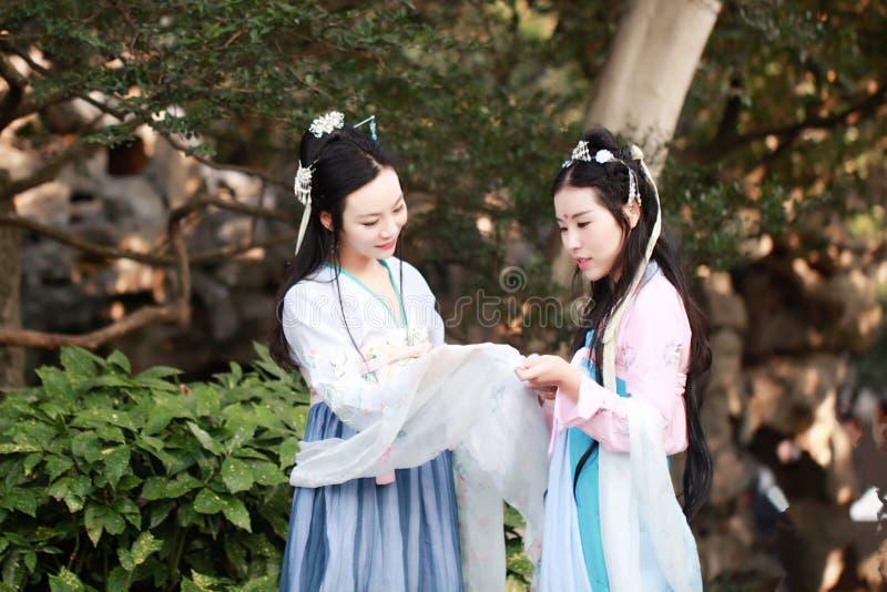 在中国传统古老服装闲谈谈话笑的接近的女朋友bestie 图库摄影