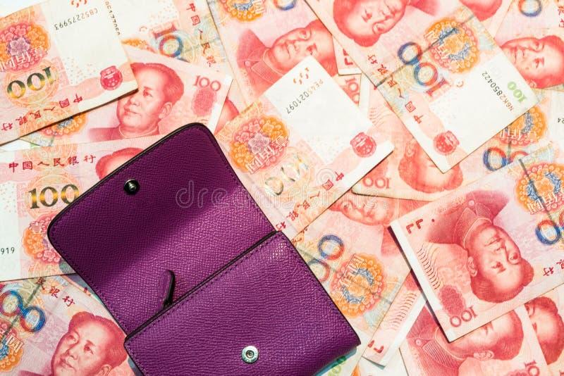 在中国元钞票安置的紫色钱包 免版税库存图片