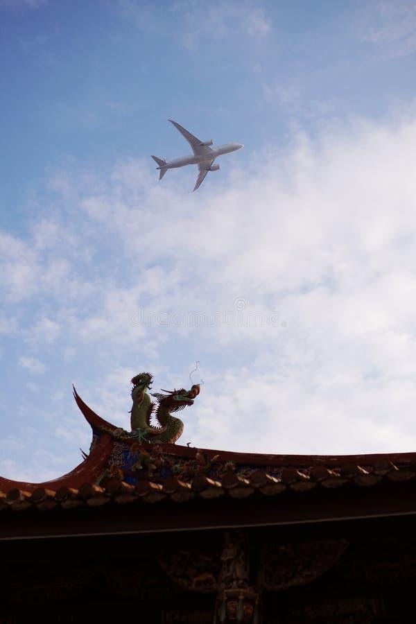 在中国寺庙上的飞机飞行 免版税库存图片