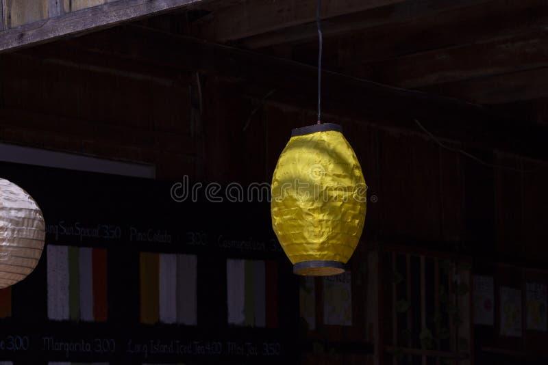 在中国风格的黄色纸灯,室外装饰 在黑暗的背景的黄色纸灯 土气手工制造装饰 库存图片