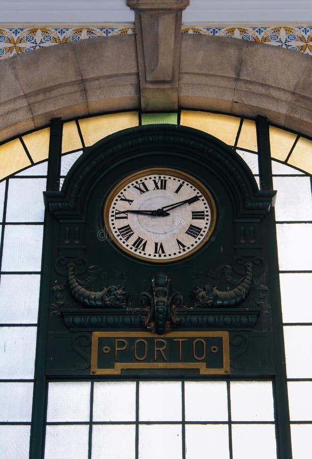 在中央火车站的老时钟在波尔图,葡萄牙 著名圣本托火车站的霍尔 古老驻地内部  免版税库存照片