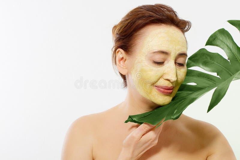 在中年妇女在白色背景隔绝的皱痕面孔的夏天防皱胶原面具 皮肤护理温泉和更年期概念 库存照片