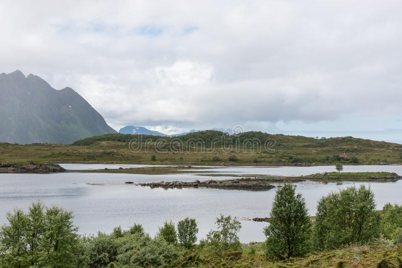 在中间的云彩盖的山夏天在挪威罗弗敦群岛海湾 免版税库存照片