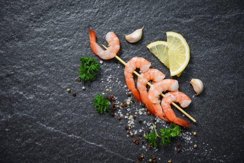 在串棍子海鲜的虾大虾烹调了草本和香料在黑暗的背景 库存图片