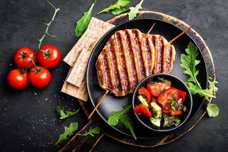 在串的水多的烤鸡肉lula kebab用在黑背景的新鲜蔬菜沙拉 免版税库存照片