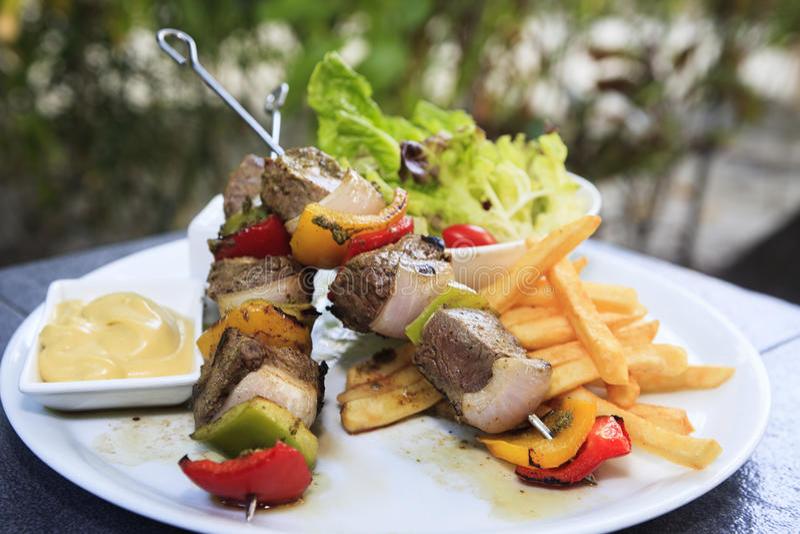 在串的羊羔烤肉串有菜的 库存照片
