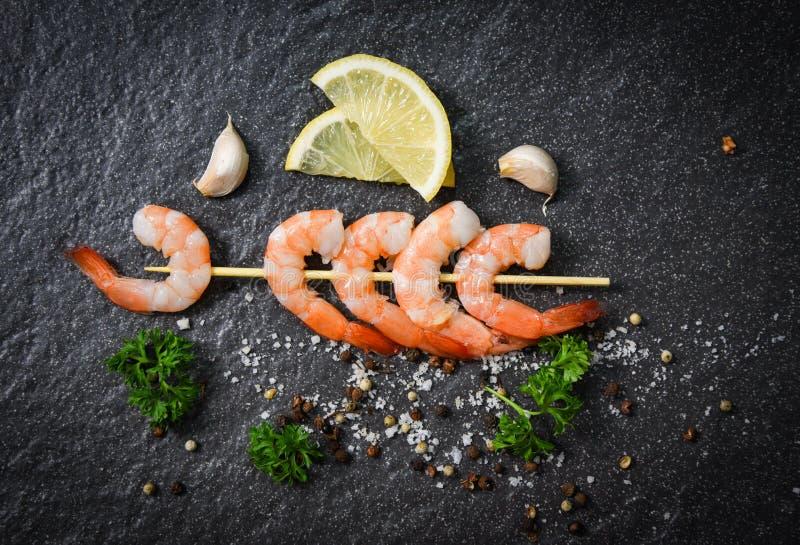 在串的虾大虾在黑暗的背景黏附海鲜烹调用草本和香料 图库摄影