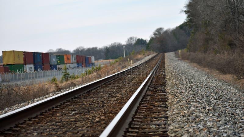在主线铁路轨道旁边的联运方式路轨围场房屋板壁 免版税库存图片