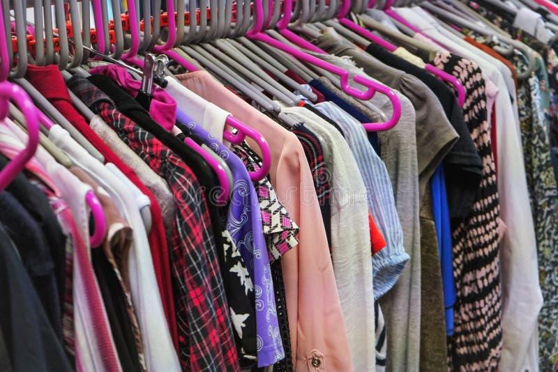 在主要桃红色挂衣架的各种各样的妇女衣物在慈善中间人旧货店里面 免版税库存照片