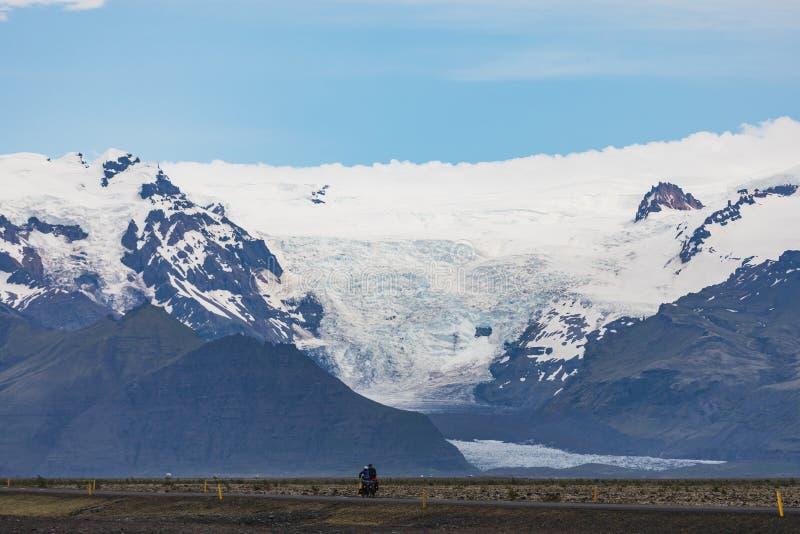 在主路,大冰川舌头的两个孤独的自行车车手  库存照片
