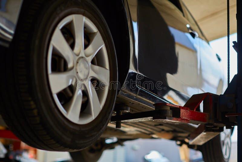 在举为修理的自动服务的汽车,车库的,关闭机械工  免版税库存照片