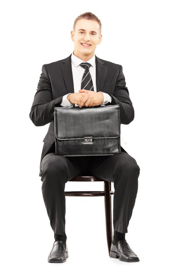 在举行公文包和等待的黑衣服的年轻商人 免版税库存照片