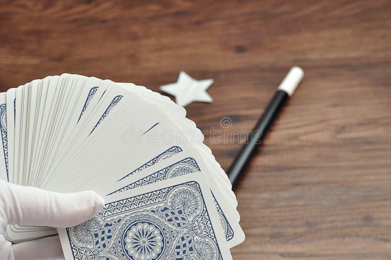 在举行卡片组魔术师递与在焦点鞭子外面 库存图片
