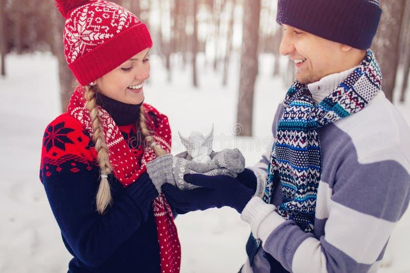 在举行在手白色天使的爱的夫妇戏弄 免版税库存照片