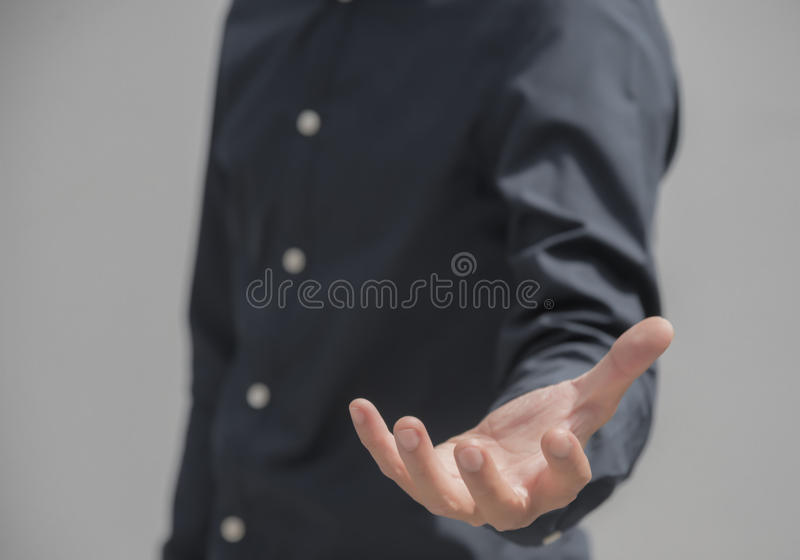 在举行某事用手的黑衬衣的企业亚洲男性 免版税库存图片