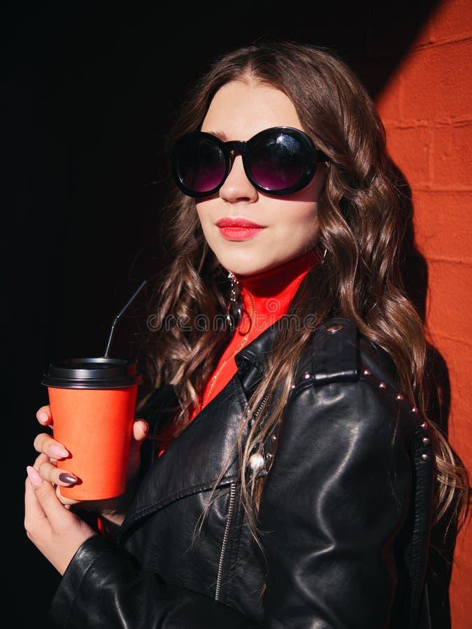 在举行红色的太阳镜时髦构成可爱的微笑红色礼服黑皮夹克的年轻可爱的棕色毛发的青少年的模型 库存图片