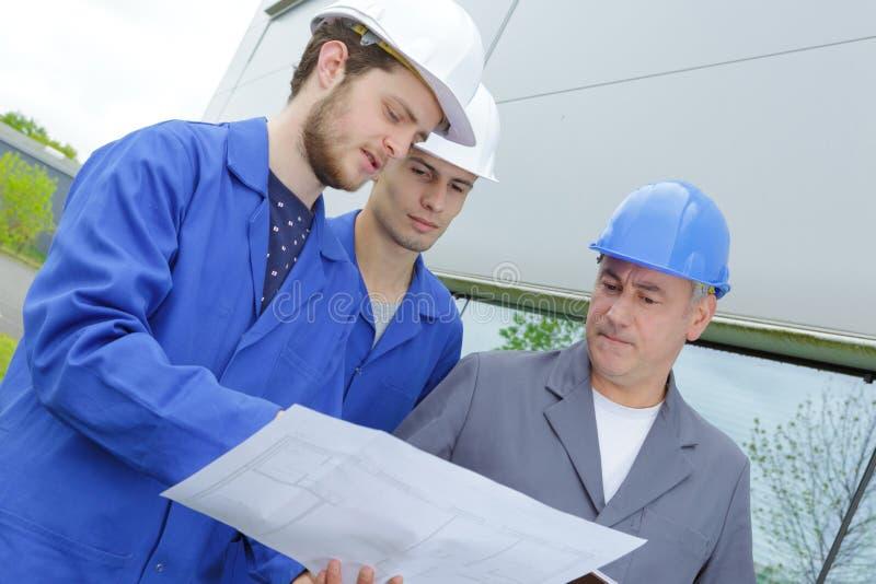 在举行计划的建造场所的建造者 免版税库存图片
