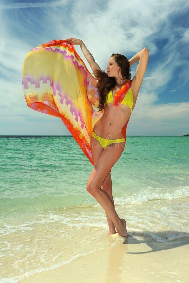 在举行pareo的黄色比基尼泳装的模型 免版税库存图片