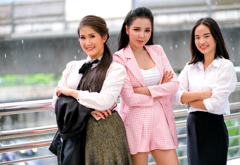 在之外的白天三个亚裔企业女孩作为确信与他们的工作并且微笑着表达愉快 免版税库存照片